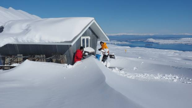 Sophie Reider and Jan Zumbrunnen clear snow from around the Von Brown Hut at Roundhill Ski Field.