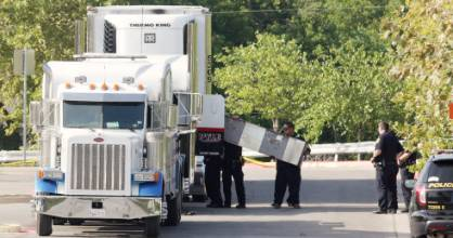 Police officers work at the crime scene after eight people were found dead inside a sweltering 18-wheeler truck trailer.