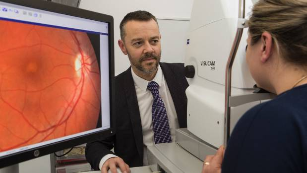 Dr Paul Baddeley conducts an eye test at St George's Hospital's eye clinic.