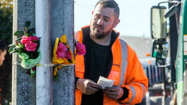 A contractor places flowers at the scene of the fatal crash. Since then memorial items have been taken.