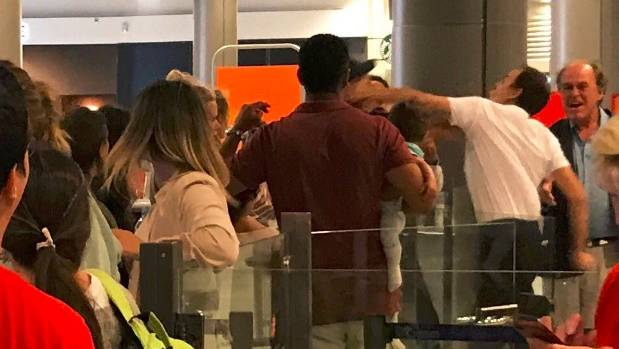 The frustrated passenger, obscured from view by other passengers, was holding a baby when the employee lashed out at him.