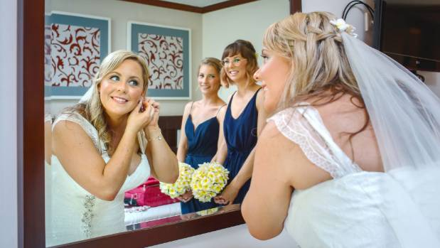 The bride puts on the finishing touches.