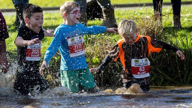 Children enter the cold water at their version of the Tough Guy and Gal contest at Linton on Friday. The main event for ...