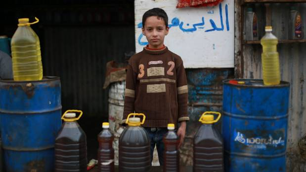 Ayman, 9, stands at his father's fuel stall in besieged east Ghouta in Rural Damascus.