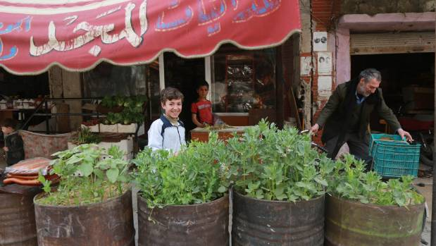 Wael, 14, stands in front of his father's shop in the besieged east Ghouta in Rural Damascus, behind the beans he ...