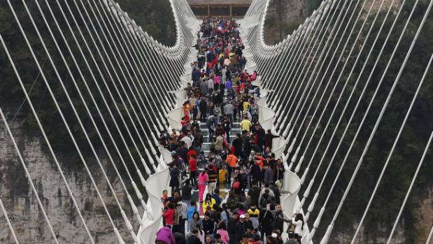 The glass-floor suspension bridge in Zhangjiajie gets packed with tourists.