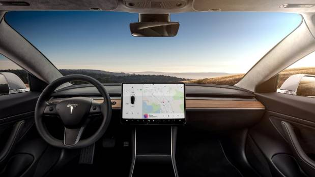The interior of the Tesla Model 3 sedan is seen in this undated handout image as the car company handed over its first ...