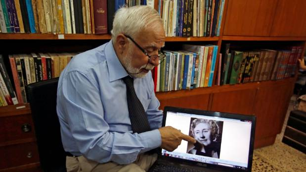 Doctor and historian Ibrahim Khalil Al-Allaf refers to Agatha Christie's picture during an interview with Reuters in Mosul.