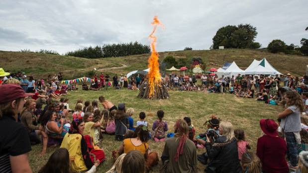 People gather for a bonfire to mark the end of the school autumn fair in April.