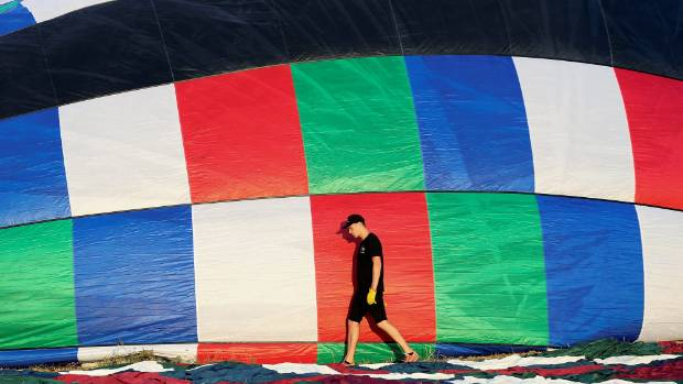 A man does one last check of his hot air balloon before he takes to the sky.