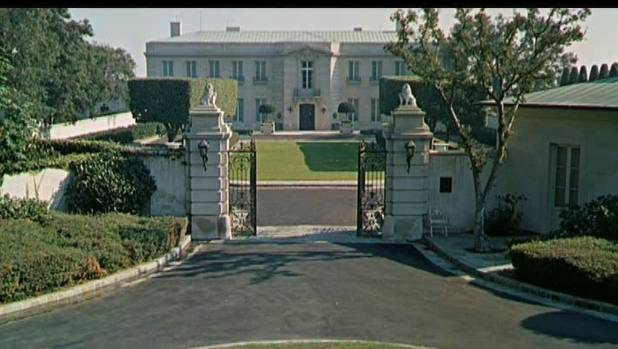The mansion hides behind a large gate.