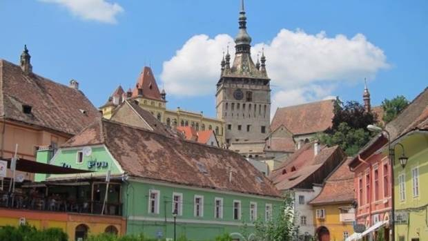The 14th Century Clock Tower of Sighisoara surrounded by historical buildings.