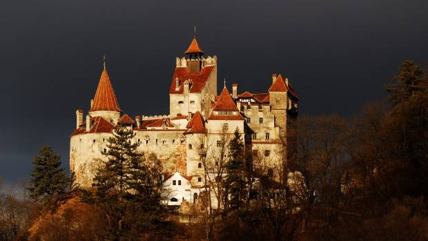 Bran Castle stands against a moody sky.