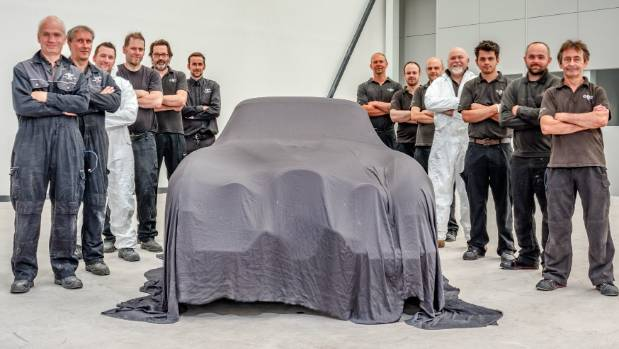 Classic Motor Cars staff pose with the under wraps, but restored, 1954 Jaguar XK120 SE by Pininfarina before it is ship ...