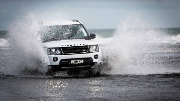 Sharon Stewart rinses-off her four-wheel-drive in fresh water after cruising Muriwai Beach.