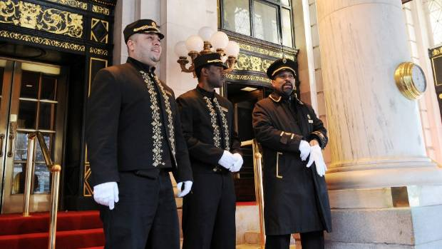 Bellhops and a doorman await guests at The Plaza Hotel.
