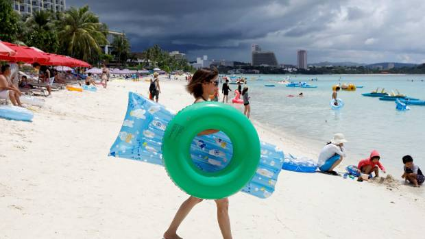 Tourists frolic along the Tumon beach on the island of Guam.