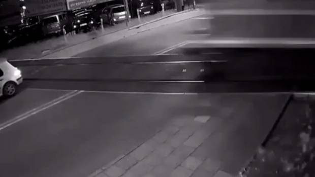 A screen grab from video footage shows a car to the left about to be clipped by a train (the blur to the right) at a ...
