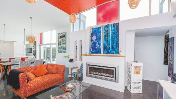 The upper void in the living area is painted red to match furnishings and the colour of the kitchen splashback.