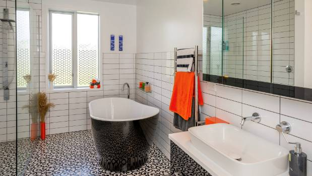 Red accents enliven the black and white bathroom.