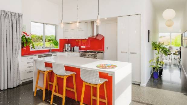 Not afraid of colour, the colours brightened the kitchen with a red colour-backed glass splashback and island front.