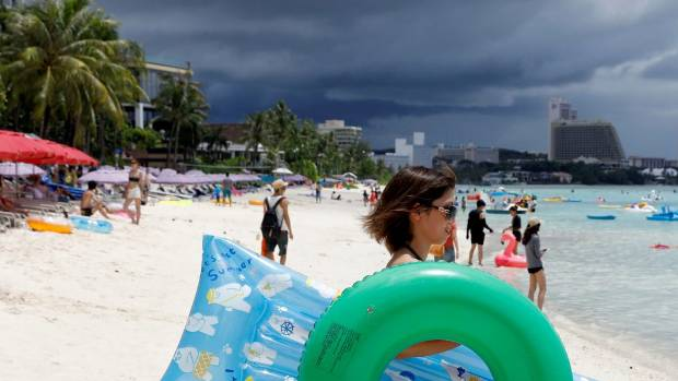 Tourists frolic along the Tumon beach on the island of Guam, a US Pacific Territory.