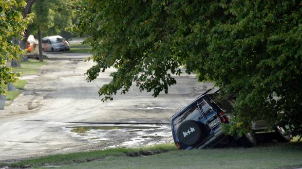 A car on Avonside Dr falls into a crack after the 2011 earthquake.