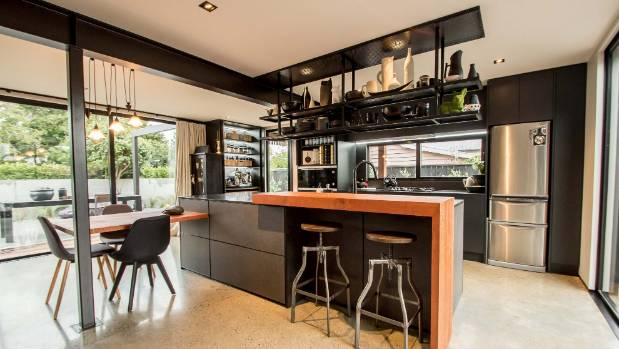 The kitchen features dark cabinetry with a natural timber waterfall bar top and table top.