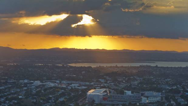 The sun sets over the Waitakere ranges in Auckland's west as the last shards of light illuminate Eden Park.