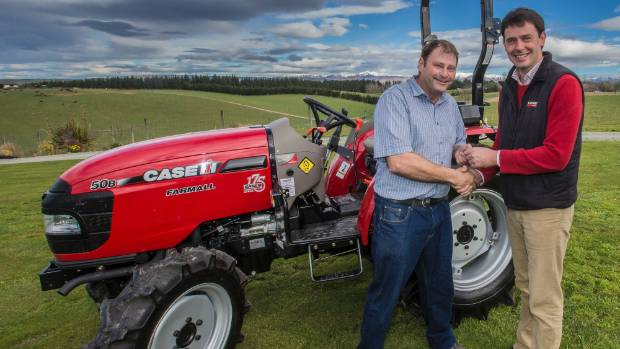 CaseIH product manager James Perry hands Nigel Gamble the keys to the new CaseIH tractor he won in a story writing ...