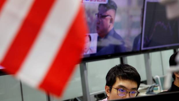 An employee of a foreign exchange trading company works in front of a monitor showing North Korean leader Kim Jong Un on ...