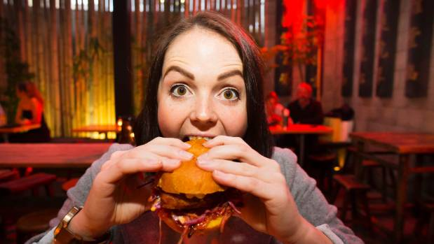 Miri Schroeter tucks into her ninth burger for the day, a lemongrass fried chicken burger from Dragonfly in Wellington.