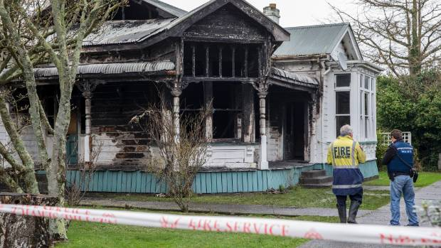 Police and firefighters working at the scene of the Ranfurly St house fire near central Palmerston North.