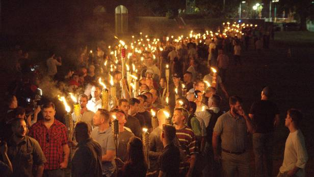 White nationalists carry torches on the grounds of the University of Virginia, on the eve of a planned Unite The Right rally.