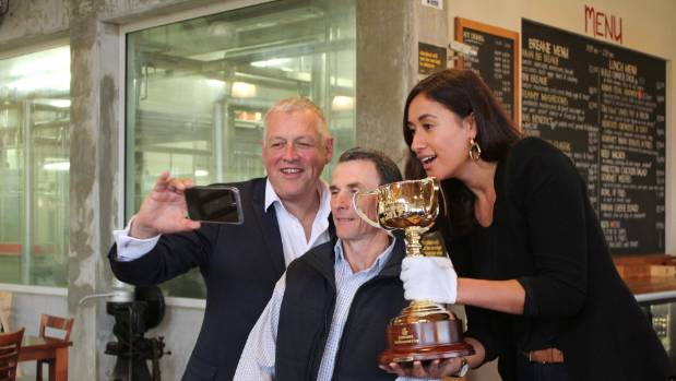 Maria holds the cup during the visit to Kaimai Cafe, with fellow tourists, her manager David Steele and Scott Seamer.
