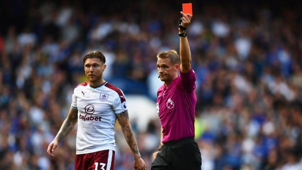 Referee Craig Pawson shows Cesc Fabregas of Chelsea (not pictured) a red card during their clash against Burnley.