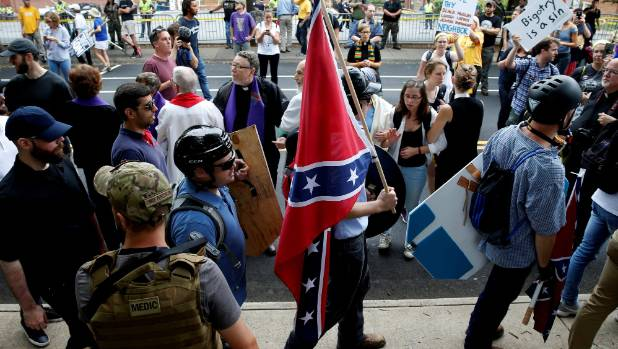 A white supremacists carries the Confederate flag as he walks past counter demonstrators in Charlottesville, Virginia.