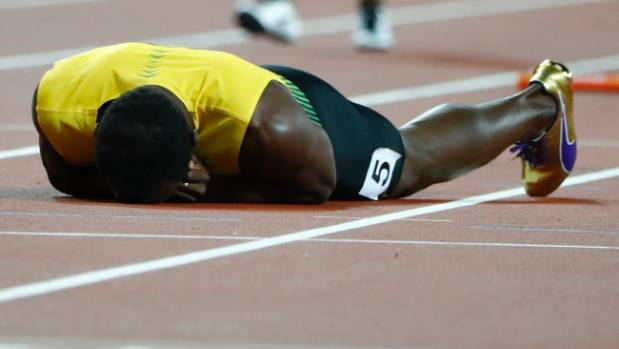 Usain Bolt lies on the track after collapsing with a foot injury in the world 4x100m final in the last race of his ...
