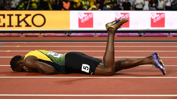 Usain Bolt of Jamaica reacts after sustaining the injury.