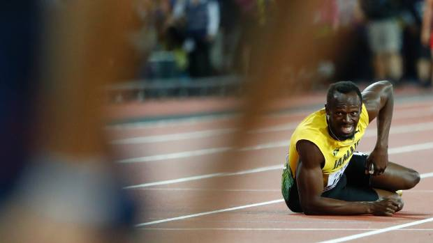Usain Bolt of Jamaica lays on the track after sustaining the injury.