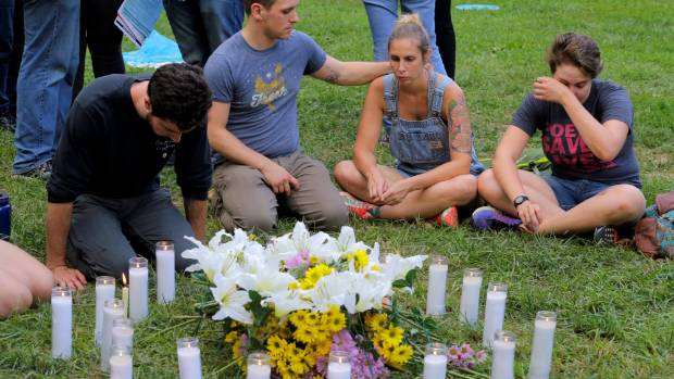 Local residents of Charlottesville sit together, pay their respects and cry at a vigil where 20 candles were burned for ...