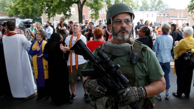 A white supremacist militia member stands in front of clergy counter protesting during rally in Charlottesville, Virginia.