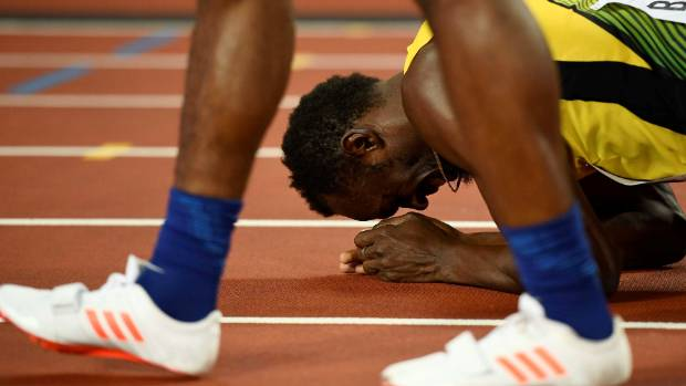 Olympic great Usain Bolt reacts in despair after injury cost him a relay medal at the world athletics championships in ...