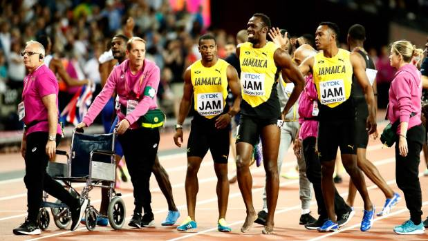 Usain Bolt of Jamaica is led off the London track, surrounded by his relay teammates.