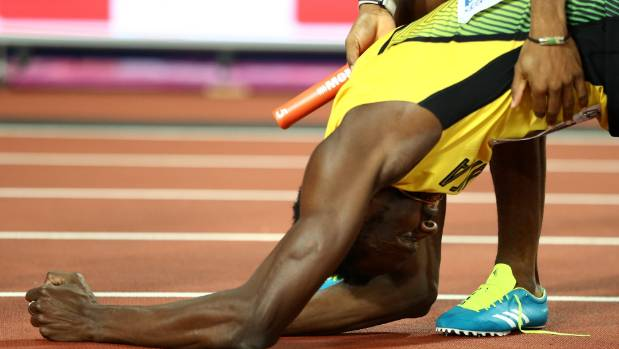 Yohan Blake checks on Usain Bolt after Bolt's dramatic injury in the world championships relay final.