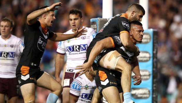 All aboard as Jack Littlejohn and Alex Twal of the Tigers celebrate with Sauaso Sue after his try against Manly Sea Eagles.