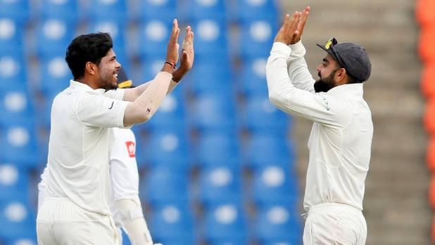 India's Umesh Yadav celebrates with captain Virat Kohli after taking the wicket of Sri Lanka's Upul Tharanga.