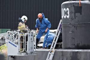 """Police technicians investigate the rescued private submarine """"UC3 Nautilus"""" in Copenhagen Harbor."""