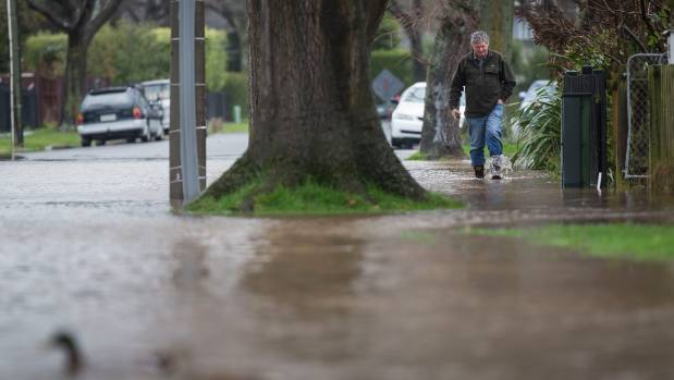 A man wades through floodwaters on Emmett St, in Christchurch.