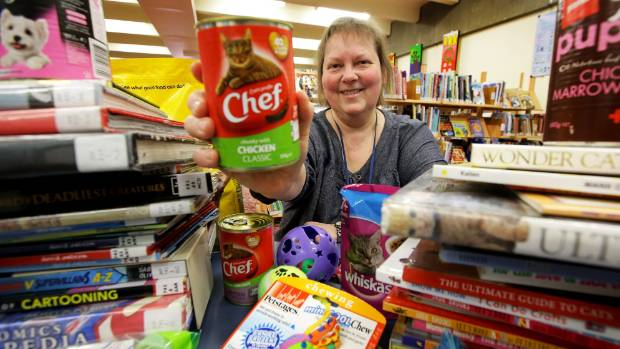 Invercargill City Libraries and Archives childrens librarian Mandy Stenton holds up a can of cat food which will be ...